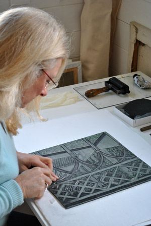 An artist works on plate for a linocut print.