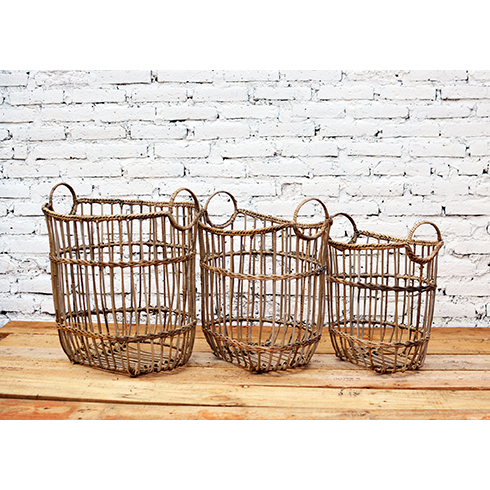 Rattan is woven over a metal frame and fixed with braided trim to form a trio of nesting baskets.